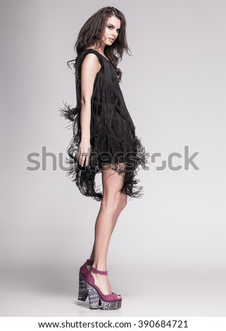 sexy slim woman model with long legs in black dress and high heels posing - stock photo