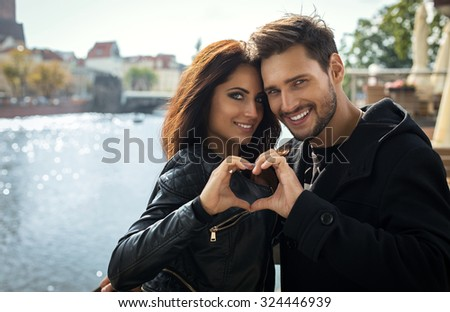 Sexy smiling couple looking through and making shape of Heart by their Hands - stock photo