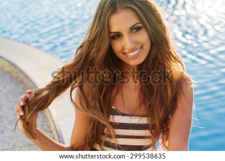 Sexy smiling girl is wearing striped fashion dress with tanned skin and makeup is sitting near pool