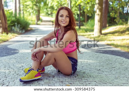 Sexy smiling girl with long hair in colorful clothing and yellow shoes sitting on the road in the park. - stock photo
