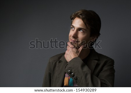 Sexy smiling handsome young man standing with his hand to his chin looking up into the air daydreaming on a dark background with copy space - stock photo