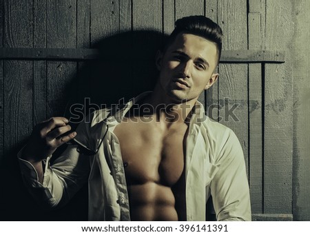 Sexy smiling sensual muscular young macho man with bare torso in white shirt and sun glasses standing indoor on wooden background, horizontal picture - stock photo