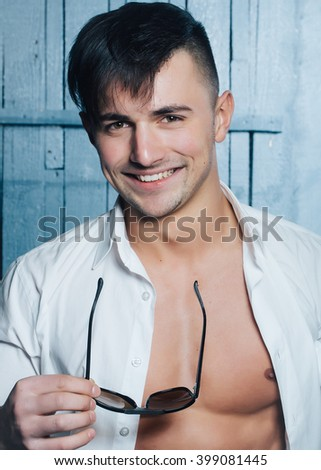 Sexy smiling sensual muscular young macho man with bare torso in white shirt and sun glasses standing indoor on wooden background, vertical picture - stock photo