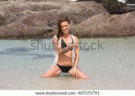 Sexy,smiling woman in bikini sitting in the sea looking at the camera - stock photo