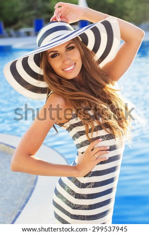 Sexy smiling woman is wearing stripped dress and hat with tanned skin and perfect figure is standing near pool, summer time