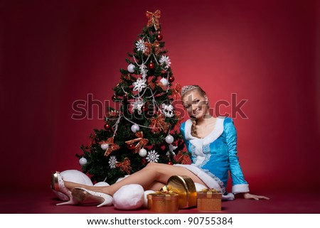 sexy Snow Maiden sit on red with new year tree - stock photo