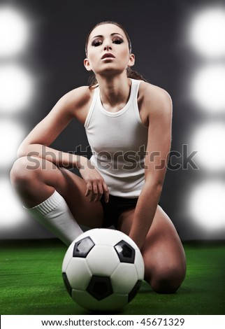 Sexy soccer player, woman on playing field - stock photo