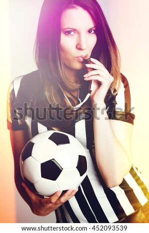 Sexy soccer referee girl blowing whistle - stock photo