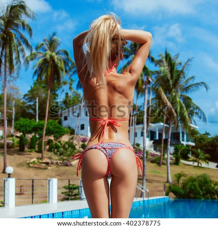 Sexy sporty tanned back of young blonde woman in bikini posing on luxury pool on tropic island vacation  - stock photo