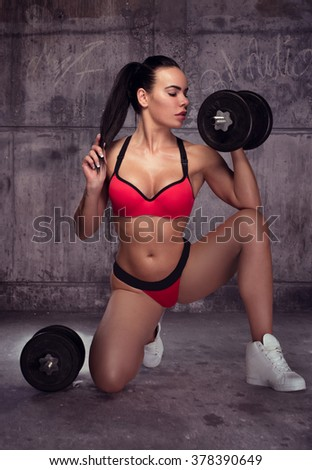 sexy sprorty brunette posing in rusted abandoned garage holding dumbbells - stock photo