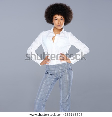 Sexy stylish beautiful African American woman with an attitude standing with her hands on her hips and a confident serious expression, square format on grey - stock photo