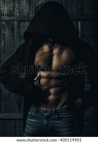 Sexy stylish strong sensual muscular young macho man with bare torso in sweater with hood on head standing indoor on wooden background, vertical picture - stock photo