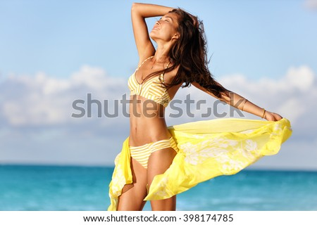 Sexy suntan woman relaxing enjoying sunset on beach with beachwear cover-up wrap showing slim bikini body for weight loss and skin care epilation concept. Asian model sunbathing during summer holiday. - stock photo