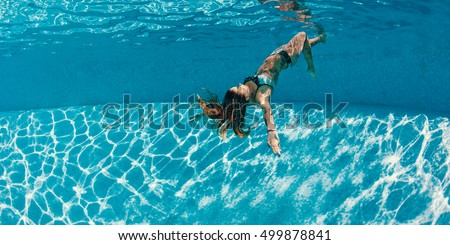 Sexy tattooed woman portrait wearing bikini upside down underwater in swimming pool. Vacation, fun, lifestyle concept.