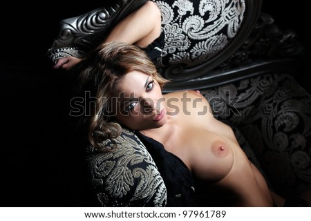 Sexy topless woman lying in a luxurious chair - stock photo