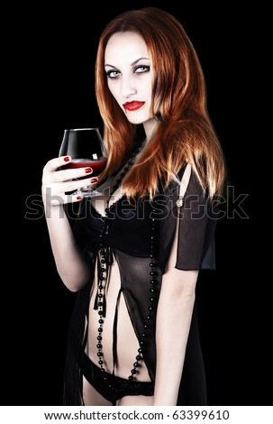 sexy vampire girl with glass of blood - stock photo