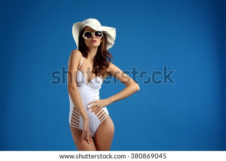 Sexy vogue girl in white lingerie, hat, sunglasses on blue background. iSolate. - stock photo