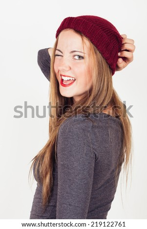Sexy winter young woman in grey dress and wool cap winking - stock photo