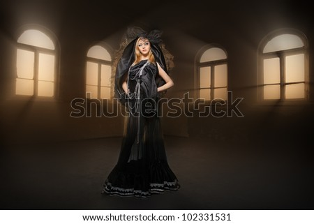 Sexy witch dressed up in black dress covered in smoke - stock photo