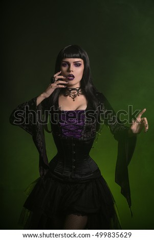 Sexy witch in a corset and velvet shirt with long sleeves, copy-space for your text