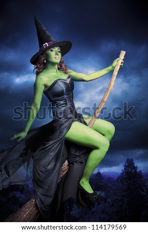 Sexy witch on a dark background - stock photo