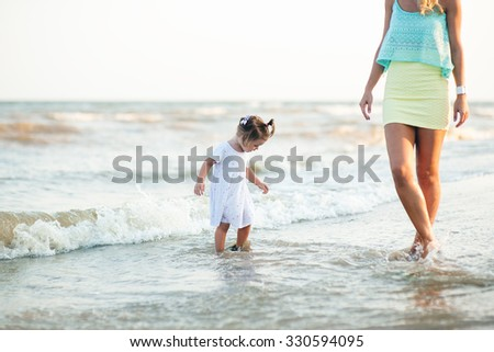 Sexy woman and little girl in a dress playing on the beach together.  - stock photo
