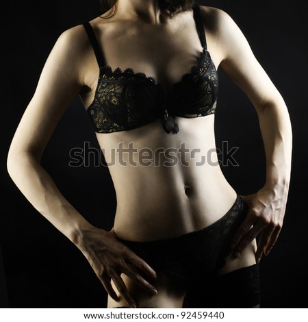 Sexy woman body in black lingerie isolated on black background.
