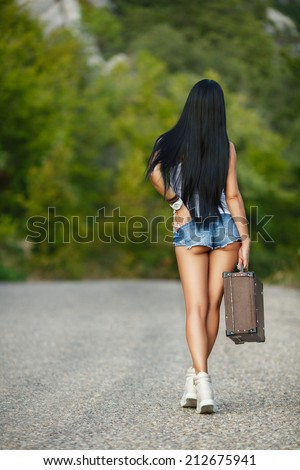 Sexy woman body in jean shorts. The model is back. Lonely girl with suitcase at country road.. - stock photo