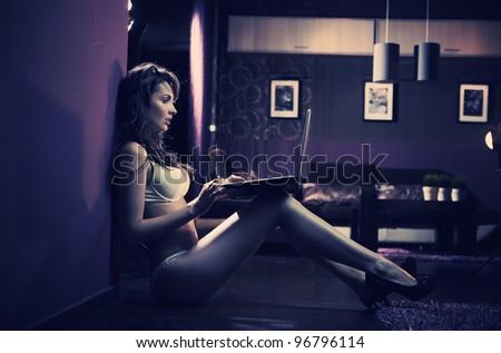 Sexy woman browsing internet late night - stock photo