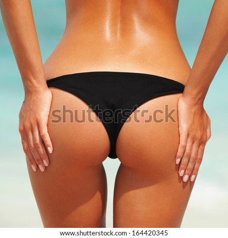 Sexy woman buttocks on the beach background - stock photo