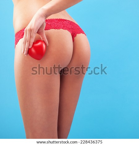 Sexy woman buttocks on the blue background holding little heart - stock photo