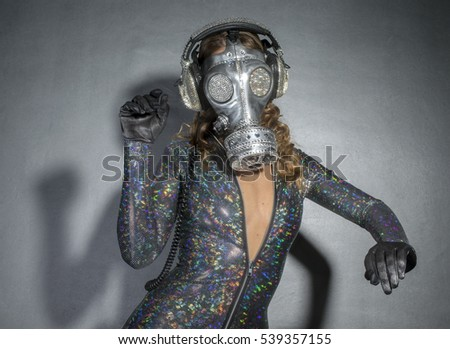 sexy woman dances with a gas mask covered in sparkling crystals. this is a special handmade item from our studio. how to survive the apocalypse in bling bling style