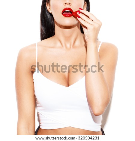 Sexy woman eating strawberry closeup. Red manicure and lipstick. Desire and sensuality. Isolated on white background - stock photo