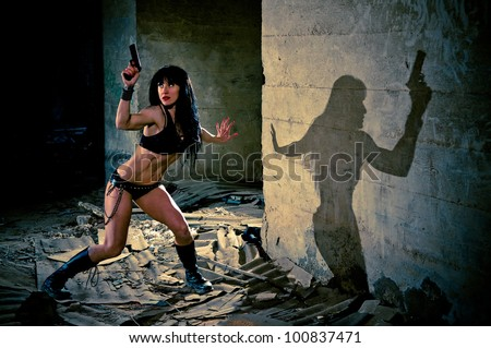 Sexy woman holding a gun wearing skimpy bikini looks furtively behind her in a dark alleyway. - stock photo