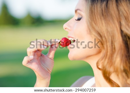 Sexy woman holding a tasty cherry on white background. Close-up portrait of beautiful woman's face eating a cherry. - stock photo