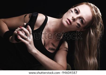 Sexy woman holding gun on dark - stock photo