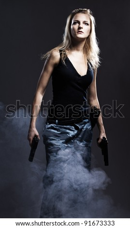 Sexy woman holding gun with smoke - stock photo