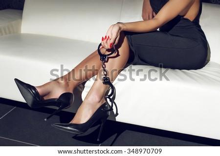 Sexy woman holding handcuffs on sofa, bdsm - stock photo