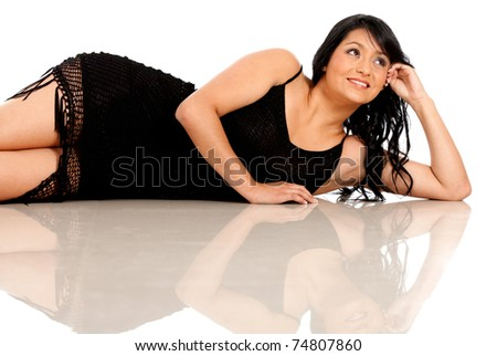 Sexy woman in a black dress lying on the floor thinking - isolated