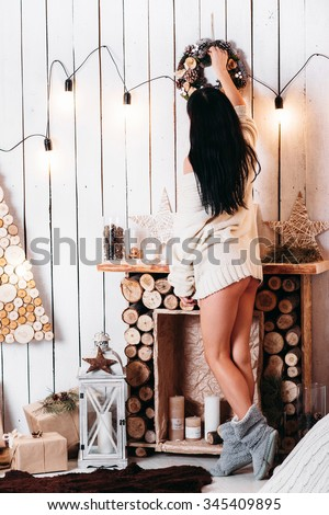 Sexy woman in a white knit sweater with a slender figure decorate the house for Christmas. the background is made of eco-friendly materials in a modern loft-style - stock photo