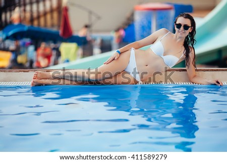 Sexy woman in bikini enjoying summer sun and tanning during holidays near pool. Top view. Woman in swimming pool. Sexy woman in bikini.