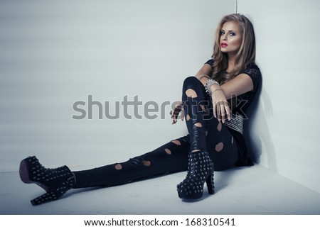 Sexy woman in black clothes in dark room