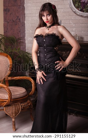 Sexy woman in black dress sitting near piano. - stock photo