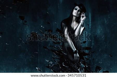 sexy woman in black hat with broken glass in dark room - stock photo