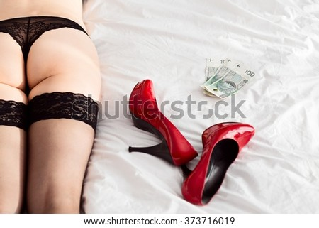 Sexy woman in black lingerie on bed. High heels and Polish money zloty next to her. Prostitute concept  - stock photo