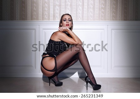 Sexy woman in black stockings squat at vintage wall - stock photo