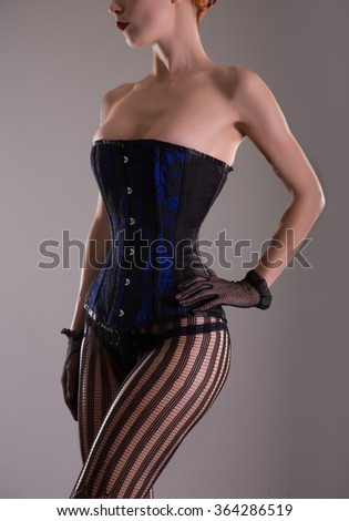 Sexy woman in blue corset and black lingerie, studio shot  - stock photo