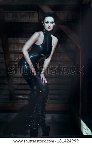 Sexy woman in catsuit posing in dark - stock photo