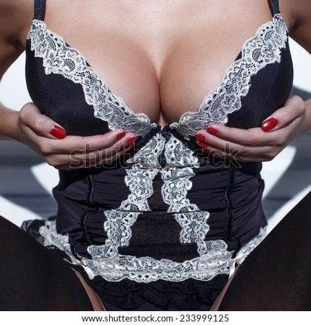 Sexy woman in corset holding her huge breasts, closeup - stock photo