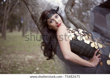 Sexy woman in fashionable clothing lying on a tree branch - stock photo